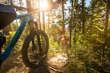 front tire of mtn bike tire with biker in front riding down forested trail with sun light peaking through the trees