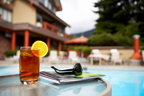 ice team with lemon by magazine by pool with hotel in background