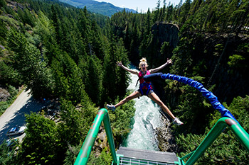 view from jumping point with spread eagle jumping women on bungee cord, creek and trees below