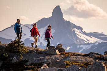 one guy and 2 girls hiking in the alpine with Whistler Peak in the background
