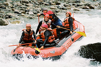group of smiling folks going through rapids