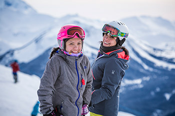 smiling mother daughter standing in ski wear on top of the world with moutains behind